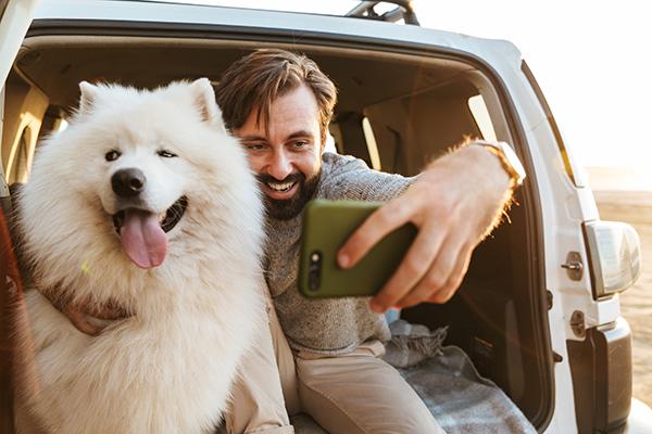 man-with-dog-samoyed-outdoors-at-the-beach-3737U6E.jpg